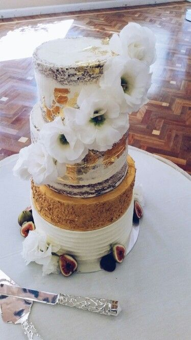 4 tier gold pebble sequin white wedding cake. Gold leaf detail on naked cake tiers