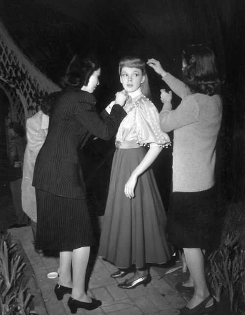 Judy Garland getting her costume and make-up primped before a Halloween scene in 'Meet Me in St. Louis' (1944).