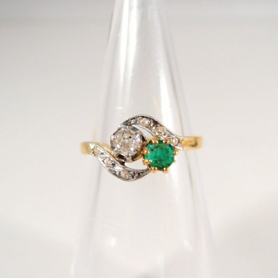 This is a splendid French Toi et Moi crossover ring. It is crafted in the finest 18K solid gold material and is adorned with two gorgeous gems.  The bypass ring is stamped with the French eagle head assay stamp and also shows the number 11957 inside the shank. This may indicate that this high quality ring was made according to certain specifications and for a certain buyer. It may have been given as an engagement ring, as was the custom in those days.  The ring features two beautiful gems…
