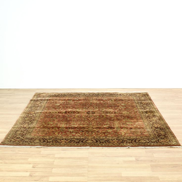 This large rug is hand tied in a durable rust, tan, green and brown finish. This Asian area rug has white fringe edges, striped border trim and floral leaf accents. Perfect for adding warmth and texture to a space! #asian #decor #rug #sandiegovintage #vintagefurniture