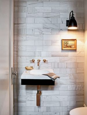 Marble tiled wall, brass fixtures, and a great light in a tiny bathroom #jeffreyalanmarks #JAM #homedecor