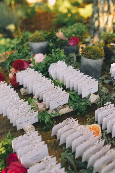 Wedding escort card idea - romantic + nature-inspired escort cards - white cards with tree slices, greenery and rose details {Black & Hue Photography}