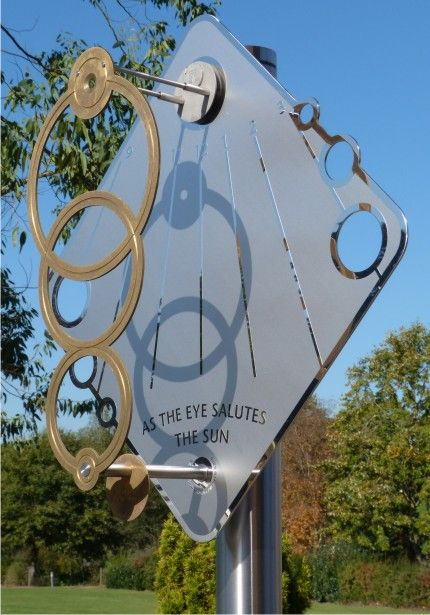 'Orbit' vertical sundial with circling shadows in October sunshine. On display at King Edward's School, Witley, Surrey, England.