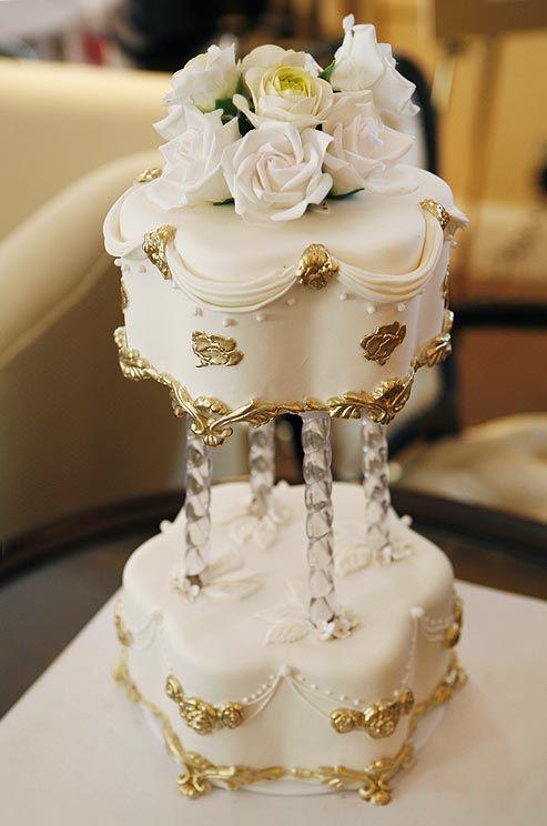 Metallic gold decorates a white miniature cake with dramatic flourishes, draped fondant and ornate trim.