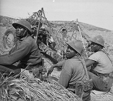 Senegalese troops of the Free French forces at the time of the inspection by General Leclerc in Tunisia, during World War II. Photograph taken on 19 May 1943 by M D Elias.  Photo credit National Library of New Zealand.