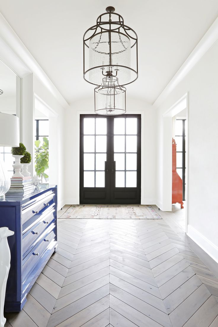 Beautiful Entryway Featuring Double Front Doors Hanging Light Fixtures And Chevron Flooring