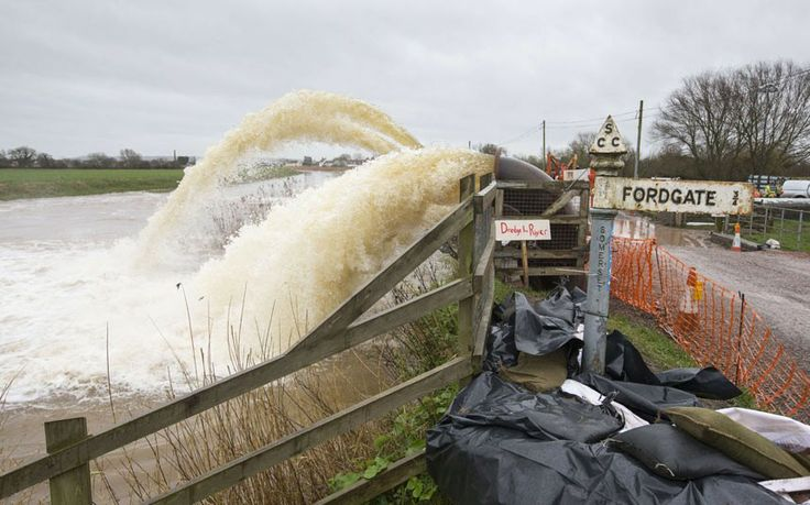 Flood water is pumped from fields into the River Parrett at Northmoor Green in Somerset, southwest England, on February 6, 2014 by a sign th...