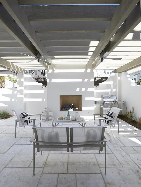A Gray Wash Pergola Hangs Over A Patio Filled With Sleek White Outdoor  Furniture Facing A