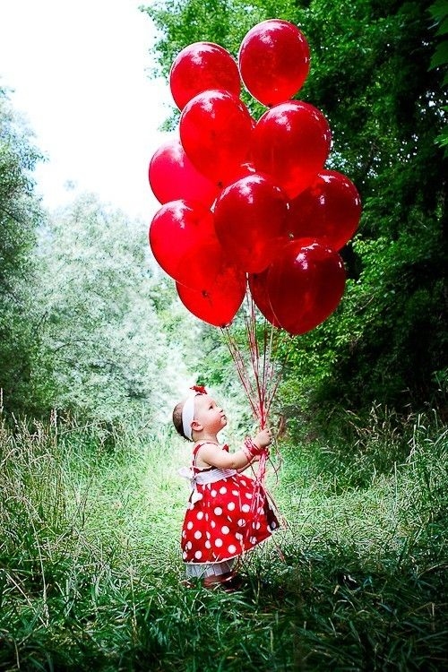 Baby and red balloons