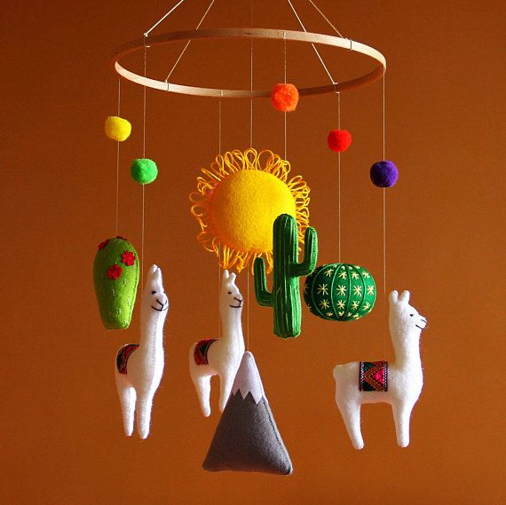 Bright and sunny baby mobile for South American nursery. The mobile features 3 white llamas with bright blankets on backs, 3 cactus, a sun, a mountain and 6 bright yarn poms. Sizes (please note, that because the item is hand-made, there may be slight deviations from listed below