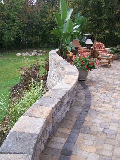 Raised Patio With Steps: Extensive Use Of Color In The Wall And Pavers Takes This