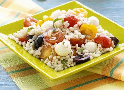 Pour préparer cette recette de salade, il vous faudra : des grains de blé, des billes de mozzarella, des tomates cerises rouges, des tomates cerises jaunes, des olives noires dénoyautées, une gousse d'ail, des brins de basilic, de l'huile d'olive, du sel et du poivre du moulin.