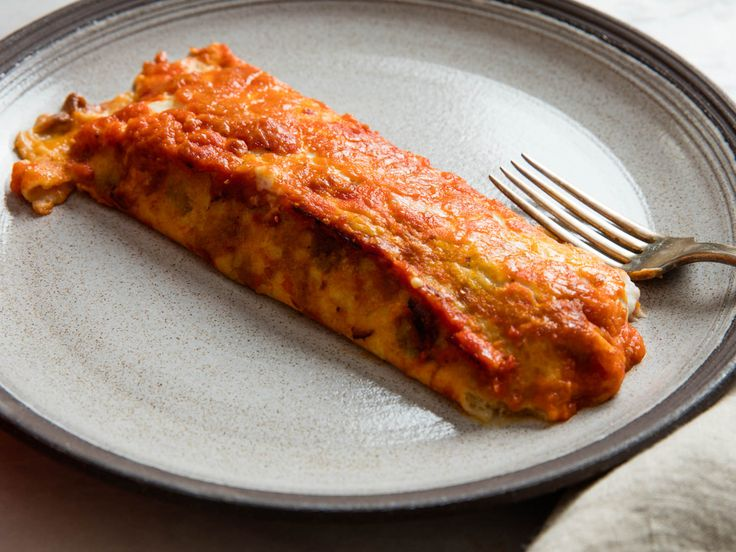 This crepe-style manicotti dish features tender thin pancakes rolled around a rich and creamy veal ragù, layered with tomato sauce, and baked until bubbling and browned.