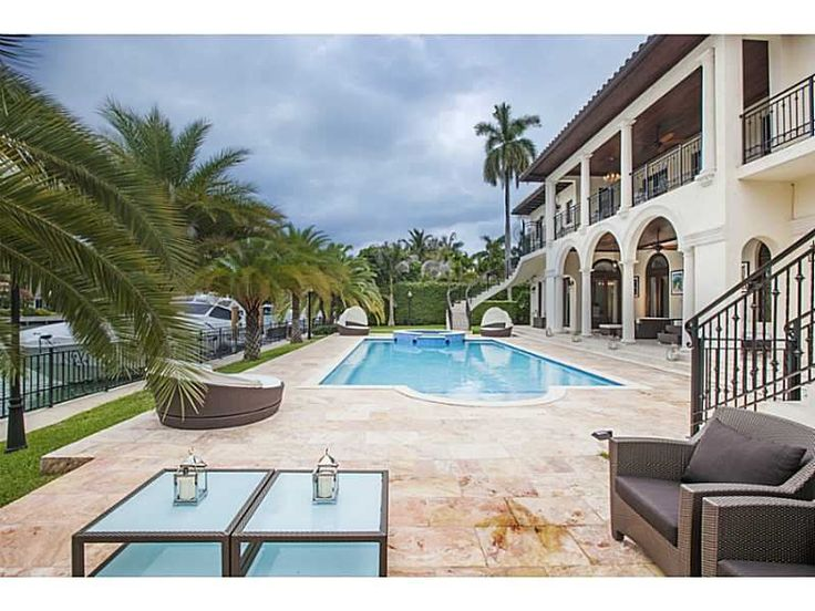 A Mediterranean style outdoor living and pool area with waterfront views. Miami Beach, FL Coldwell Banker Residential Real Estate $19,000,000Miami Beach, Miami Villas