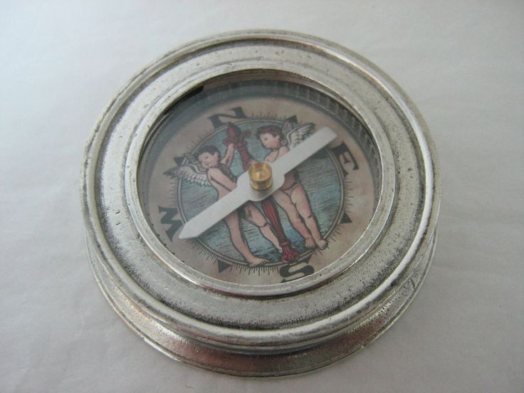 """6.5cm - 2-1/2"""" diameter. Ornamental Pewter Compass with cherub design background. Produced by Italian craftsmen.  95% Tin and Lead Free. The marks and aging that occur naturally over years are reproduced on the pewter surface. Traditional finish (unpolished finish) Hand crafted reproduction piece made in Italy representing centuries of European design. Stamped with Cosi Tabellini makers mark."""