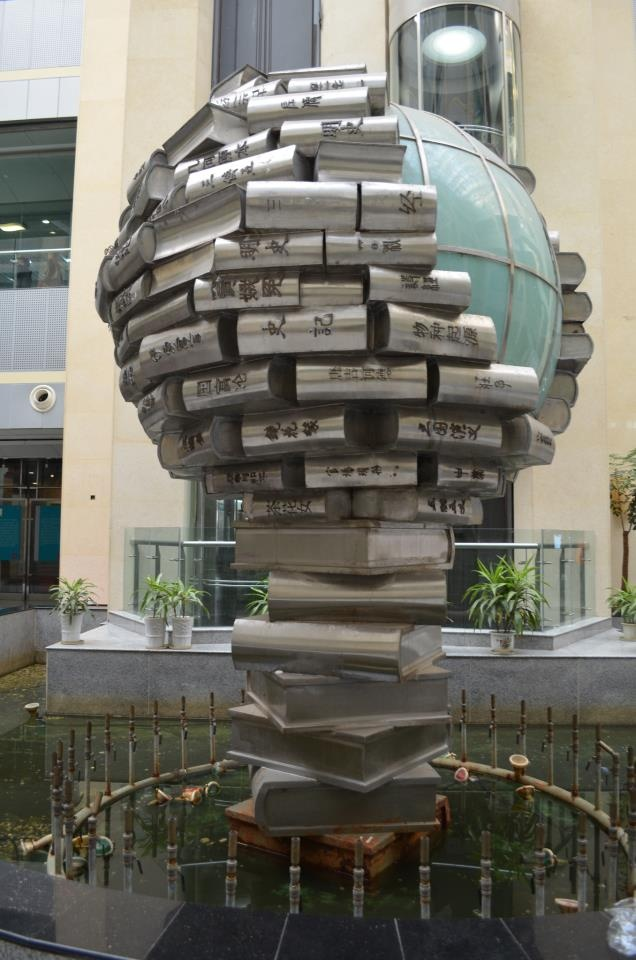 fountain with sculpture of books wrapped around a globe at its centre, at the library of the city of Jiangsu, China