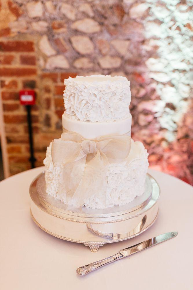 Traditional Three Tier Wedding Cake with Ribbon & Ruffled Layers | Classic Wedding | Rustic Barn Reception | Farbridge Barn in Sussex | DIY paper flower wall backdrop | Images by Joanna Nicole Photography | http://www.rockmywedding.co.uk/rachel-matthew/