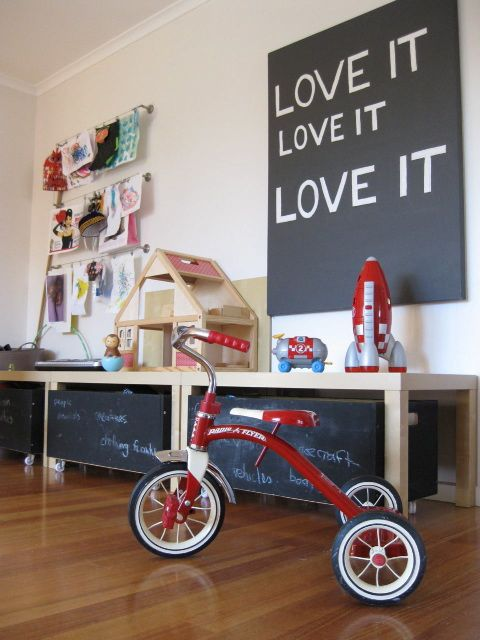 """Lisa Barrett's retro-modern-chic playroom provides plenty of storage space for her toys and still has room to play. From the chalkboard-painted cubbies to the art display area and the """"Love It"""" print, the room gives tots ample opportunity to express their creativity."""