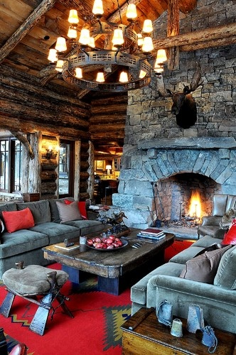 Rustic-styled living room with stone fireplace, iron chandelier, natural wood surfaces and earth toned furnishings