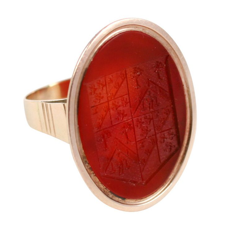 Georgian Ring Grand Acre Agricultural Intaglio Ring. A Georgian carved carnelian intaglio abundant with crisp carved decipherable symbols. We can read but not fully understand the why or wherefore of the signs. This is a rebus or puzzle in which the symbols had meaning and utility ages ago, yet are lost today. The motif is clearly agricultural. A large crest outlines the border of the intaglio. Within are four sections, each further divided some four or five times. Rows of farm plantings are…