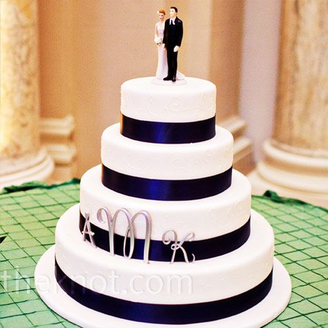 Set off by a green pin-tuck tablecloth, the four-tiered white buttercream cake was wrapped in navy ribbon and decorated with the couple's monogram.