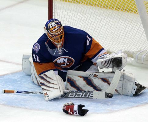 New York Islanders goalie Jaroslav Halak (41) slaps aside a shot on goal by Washington Capitals right wing Joel Ward (42) in front of the net during the second period of a game on Monday, Dec. 29, 2014 at Nassau Coliseum.