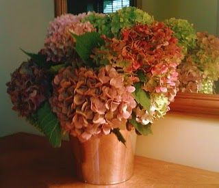 Just add a couple of tablespoons of glycerin to the water in the arrangement, the blossoms absorb it and the flowers will be preserved.