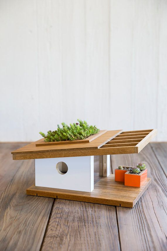 This birdhouse was designed by Douglas Barnhard. This mid century modern birdhouse is made with bamboo and high end glossy white and orange laminate. It has a floor to ceiling viewing window made of plexiglass and includes movable planter box and roof for succulents. (succulents not included) This birdhouse is perfect for any wanting to accent there modern outdoor space. Dimensions: (photo by E. Spencer Toy/Sunset Publishing)