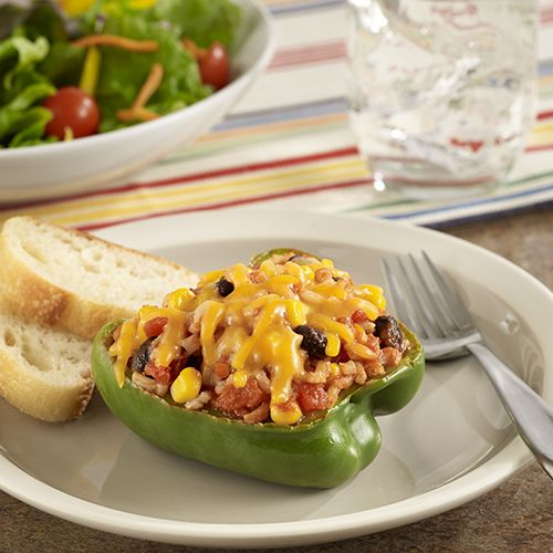 A heart healthy recipe for stuffed peppers filled with brown rice, vegetables and cheese for a Mexican flavor influence