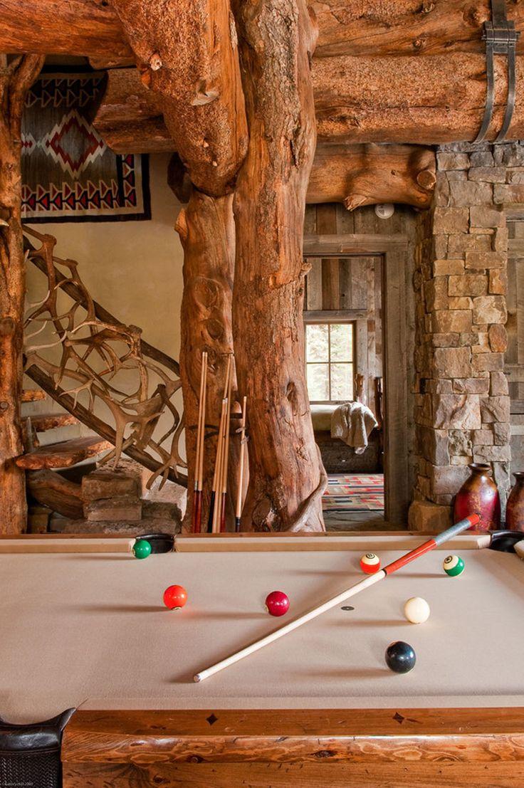 Dans le grand séjour rustique on trouve une table de billard et des poutres apparentes imposantes