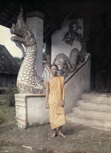 "Autochrome: W. Robert Moore. A monk stands outside of a temple decorated with serpents, or, ""naga."" Siam."