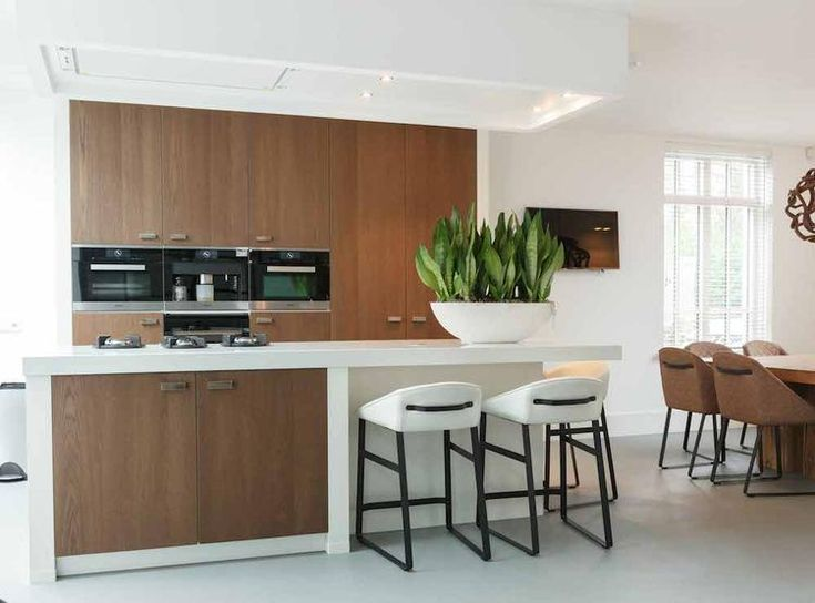 Plaatje van een keuken. De houten deurtjes in de witte kaders geven deze keuken een heel eigen gezicht. Mooi ook die luifel boven het eiland met een afzuighemel daarin weggewerkt. Keukendealer: www.vanginkelkeukens.nl