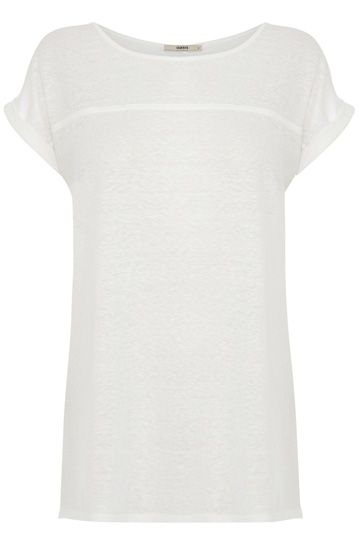 This simple tee features a textured flower detail across the fabric. The piece features a crew neckline and short sleeve styling. The tee is complete with a modern sheer hem.