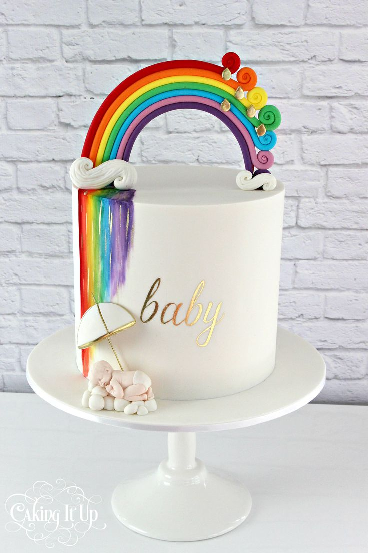 A vibrant and rainbow themed baby shower cake features a fondant rainbow topper and watercolour rainbow on cake. Hand painted gold text. www.facebook.com/cakingitup
