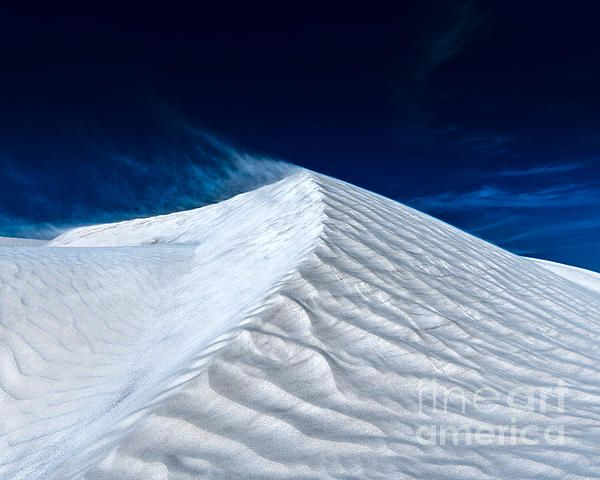 Sand blowing over a white sand dune peak, North of Perth in Western Australia.