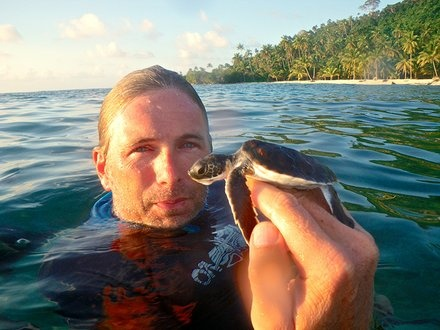 Winning the Race: Wallace Nichols greets a hatchling green turtle in the Anambas Islands, Indonesia. The Biosphere Foundation helped the community transition from a turtle-egg market to a more protective conservation model.