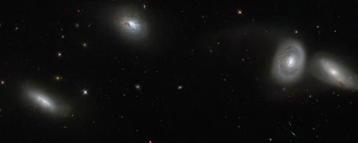 This new NASA/ESA Hubble Space Telescope image shows a gathering of four cosmic companions. This quartet forms part of a group of galaxies known as the Hickson Compact Group 16, or HCG 16 u2014 a galaxy group bursting with dramatic star formation, tidal tails, galactic mergers and black holes.