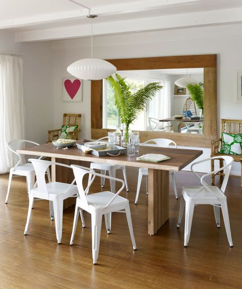 Steel bistro chairs, ordered from overstock.com, surround a white oak table from Crate & Barrel in the dining room of this New York home.