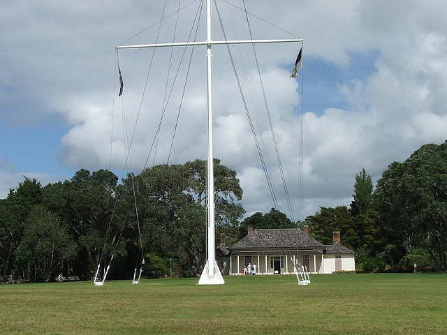 The flagstaff marking the spot where the Treaty of Waitangi was signed in New Zealand in 1840, with the Treaty House in the background, at the Treaty Grounds, Waitangi.