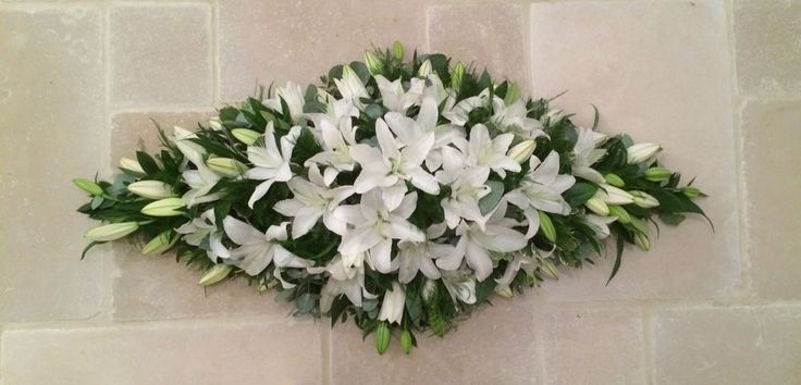 Luxury casket spray. A simply stunning coffin top spray floral arrangement. Combining elegant oriental lilies with a selection of seasonal foliage. Available in sizes: 3', 4' & 5' Colours: White or Pink