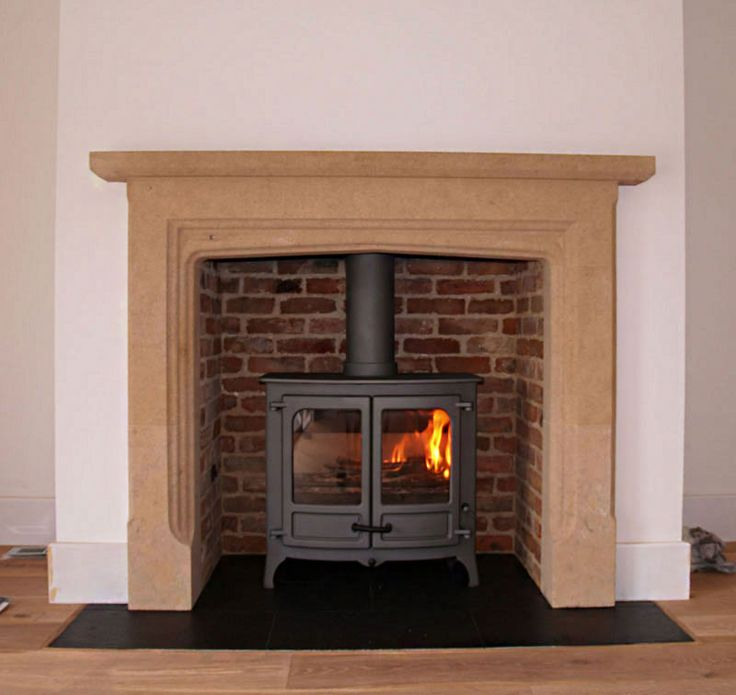English hand carved Limestone mantel with natural slate tiled hearth, reclaimed brick slip chamber and new build chimney with a Charnwood Is...