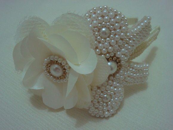 Tiara encapada em fita bege pérola com fios de pérola flor em cetim e lindo laço bordado em pérola com strass. R$ 35,00