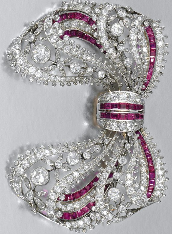 AN EDWARDIAN RUBY AND DIAMOND BROOCH, CIRCA 1910. Designed as a stylised tied ribbon bow, decorated with open work floral motifs and millegrain set with circular- and rose-cut diamonds and calibré-cut rubies. #Edwardian #brooch