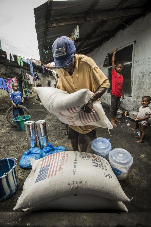 A man unloads USAID food collected at a WFP food distribution in the West Point Slum of Monrovia, Liberia, as a part of the Ebola response. (9 September 2014, Photo: WFP/Rein Skullerud)