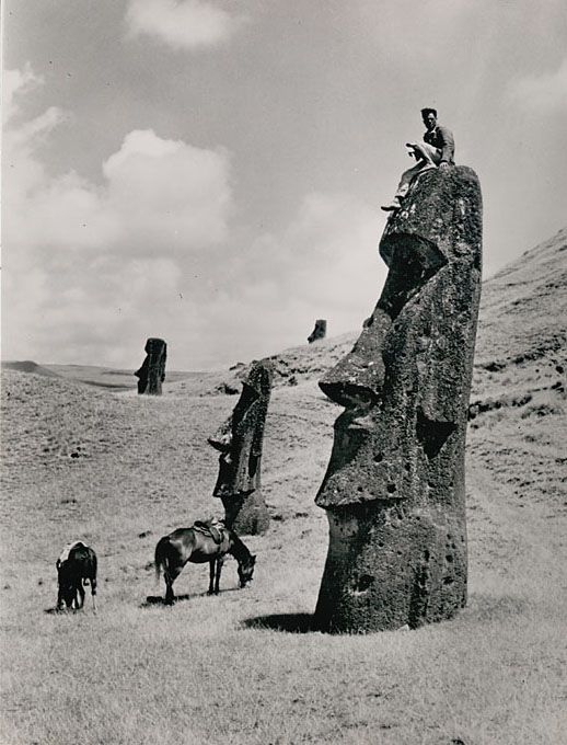 Man atop a moai (lava stone effigy) on the slope of a volcano, Easter Island (Rapa Nui), 1936, photo by Hermane Martini. (Smithsonian)