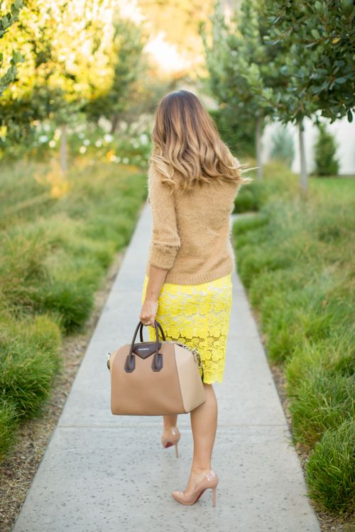 A bright yellow lace skirt styled with a camel sweater.