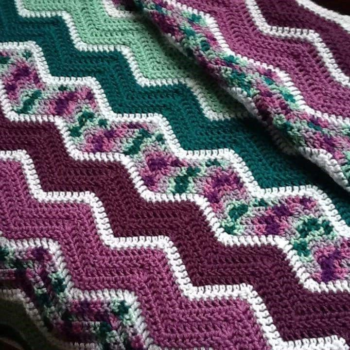 "http://m.wikihow.com/Crochet-a-Zig-Zag-Afghan. Photo by Mary Ellen Belford in Starting Chain group on Facebook. ""I Love This Yarn"". Colors: 694 Fantasy (that's the variegated), 301 Mulberry, 111 Hot Orchid, 112 Ocean, 310 Peacock, and white. 2 skeins of each color and less than one of the white. It's a simple double crochet zigzag stitch."