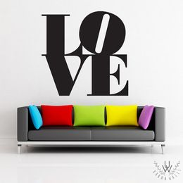 """All you need is love wall decal in black with """"LO"""" on one line and """"VE"""" on the next line. The """"O"""" is slightly tilted and the decal is behind a modern dark grey couch with multicoloured pillows on a white wall."""