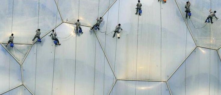 Los trabajadores limpian el exterior del National Aquatics Center, también conocido como Water Cube, en el Olympic Green en Beijing, el 18 de julio de 2008. A menos de un mes de las Olimpiadas, Beijing y las provincias vecinas han pedido a las industrias contaminantes que cierren o reduzca la producción para limpiar el aire para los atletas, y para ayudar a compensar una escasez de energía que se avecina.  REUTERS / Ge Gong (CHINA) (BEIJING OLYMPICS 2008 PREVIEW)