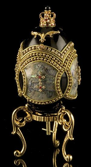 Musical egg with abalone shell panels edged with beaded gold braid. Two star-shaped jewels with ruby-coloured crystal centres adorn the middle of each shell panel. A crown-shaped jewel surrounded by golden embellishments and clear crystals sits atop the egg, which is lined with ruby-coloured velvet.